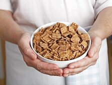 Hands holding a bowl of cinnamon flavoured breakfast cereal
