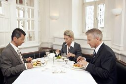 Woman and two men at a business meal