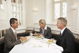 Woman between two men at a business meal