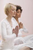 Two young women meditating with eyes closed