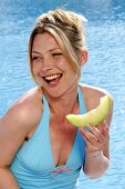 Woman with a piece of honeydew melon by swimming pool