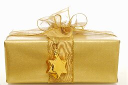 Gift in gold wrapping paper with gold star