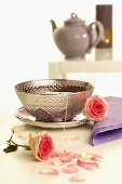 Tea in silver cup & saucer with roses, teapot, aroma lamp