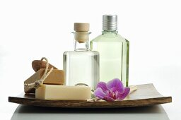 Two cosmetic bottles, soaps and orchid flower