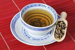 Bowl of tea with dried black cohosh root in scoop