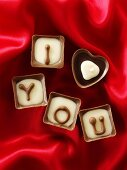 Chocolates on red fabric with the message 'I love you'