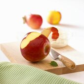 Apple, dish of quark and knife on wooden board