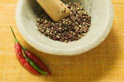 Szechuan pepper in mortar, chili peppers beside it