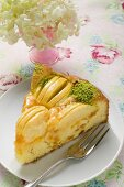 Slice of apple cake with chopped pistachios on plate