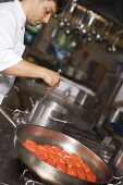 Tomatoes in frying pan, chef stirring pan
