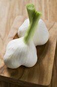 Two fresh garlic bulbs on wooden chopping board