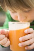 Child drinking a glass of freshly pressed apple juice