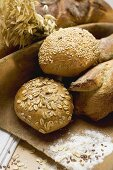 Baguettes & wholemeal rolls in wooden scoop in front of tin loaf