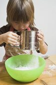 Child sieving flour into a bowl