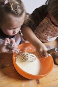 Two children stirring cake mixture with whisks