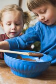 Two children making chocolate icing