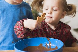 Girl dipping Christmas biscuit in chocolate icing