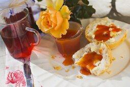 Rose hip jam on bread roll, jar of jam, rose hip tea, yellow rose
