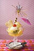 Ice cream sundae with fresh fruit and cocktail umbrella