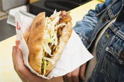 Hands holding a döner kebab in a snack bar
