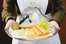 Waitress serving a cheese platter with grapes and crackers