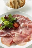 Raw ham and salami on plate, baguette slices