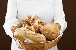 Chambermaid serving assorted bread rolls in bread basket