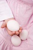 Child holding white eggs