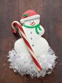 Snowman biscuit and candy cane on wooden background