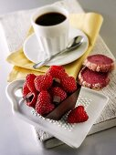 Small chocolate cake with raspberries and cup of coffee
