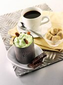 Small chocolate cake with pistachio cream, cup of coffee, sugar