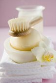 Perfumed soap in soap dish, towels, brush and windlight