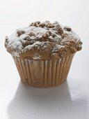 Nut muffin sprinkled with icing sugar in paper case