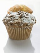 Nut muffin sprinkled with icing sugar in front of lemon muffin