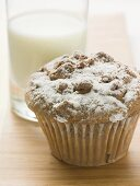 Nut muffin sprinkled with icing sugar in front of glass of milk