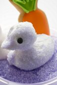 Meringue chick with purple sugar, carrot biscuit in background