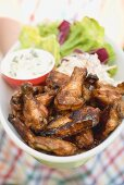 Woman holding chicken wings with blue cheese dip and salad