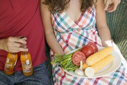 Seated couple with vegetables for grilling & bottles of beer