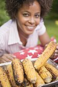 Woman taking grilled corn on the cob out of aluminium dish