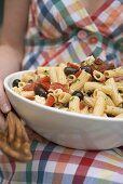 Woman holding large dish of pasta salad with olives & tomatoes