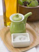 Salt, small green jug, bottle of oil and leaf salad