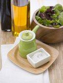 Salt, small green jug, oil, vinegar and leaf salad