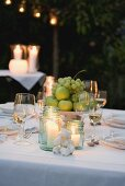 Bowl of fruit and windlights on table laid in garden