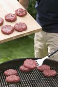 Man placing raw burgers on barbecue grill rack