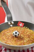 Hand holding frying pan with rösti, toy football & Swiss flag