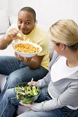 Couple on sofa with peanut puffs and salad