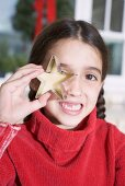 Girl holding cut-out biscuit in front of her eye