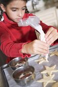 Girl icing biscuits with icing bag
