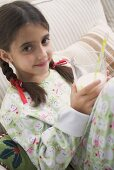 Girl holding glass of milk with straw