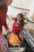 Young woman holding turkey in roasting dish, girl in background
